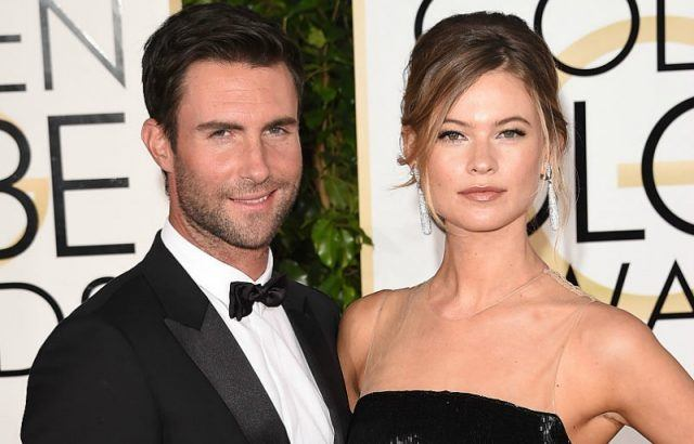Adam Levine and Behati Prinsloo pose together on the red carpet of the Golden Globe Awards.