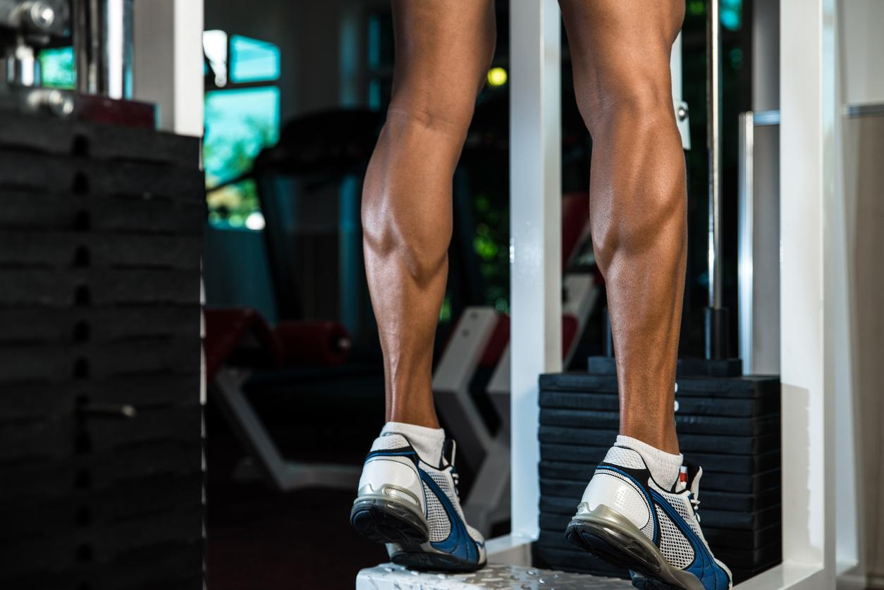 A man does calf raises at the gym