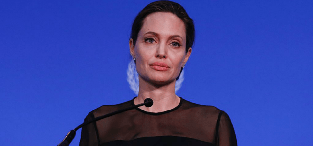 Angelina Jolie wearing a black top, set against a blue UN background.