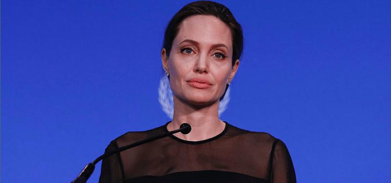 Angelina Jolie wearing a black top, set against a blue UN background