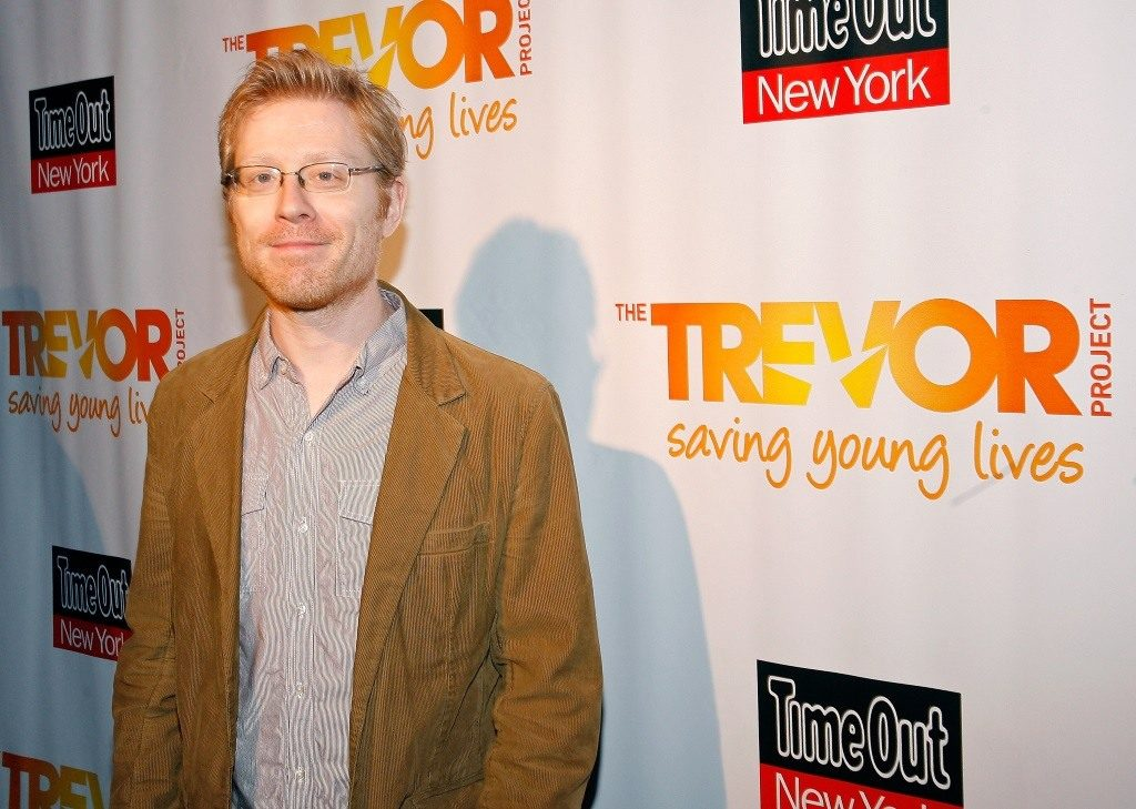 Actor Anthony Rapp on the red carpet, wearing a brown jacket and smiling for the camera