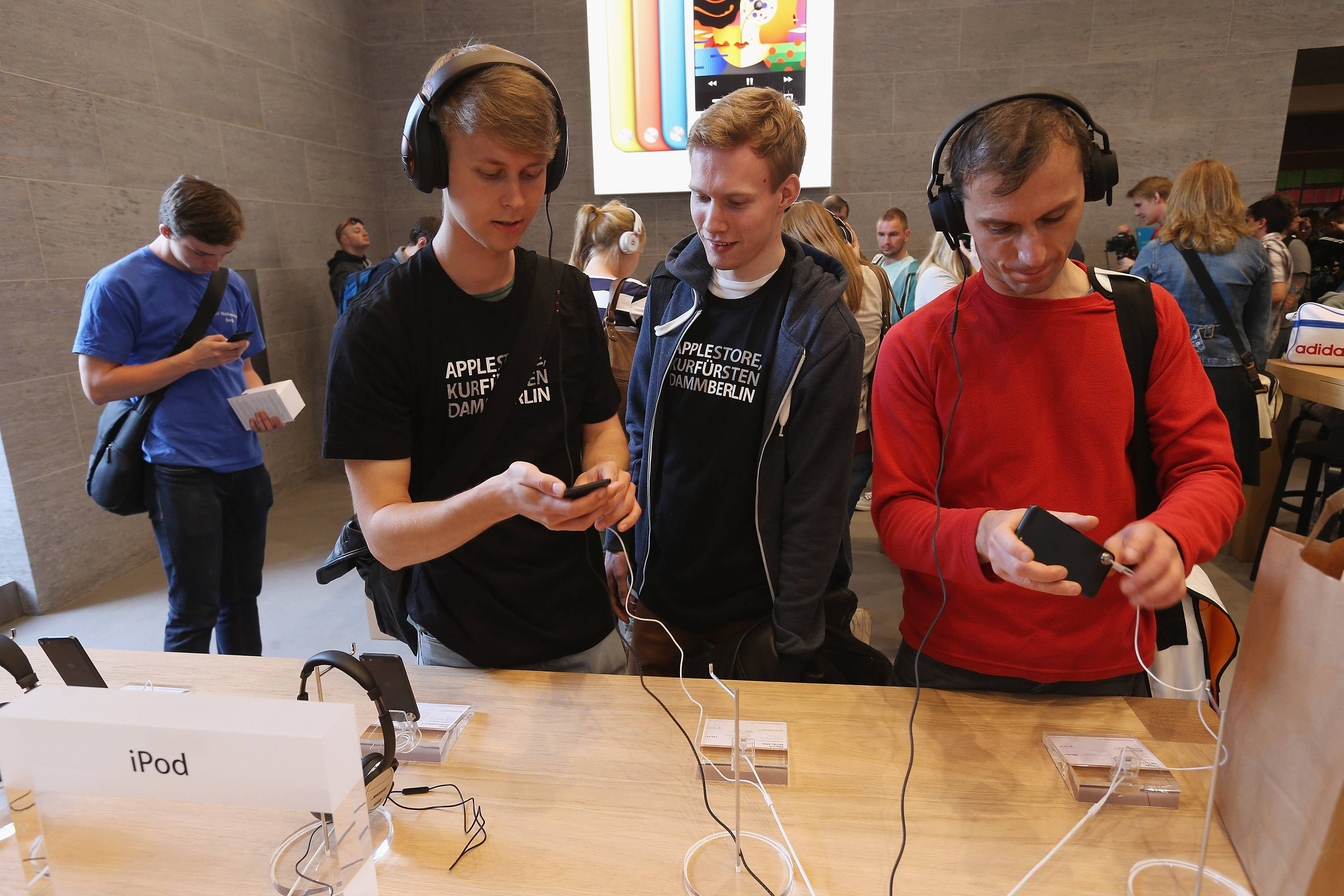 Visitors try out hifi headphones on Apple iPods at the new Apple Store