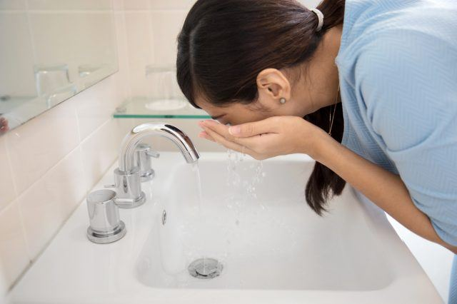 Asian woman washing her face in the sink