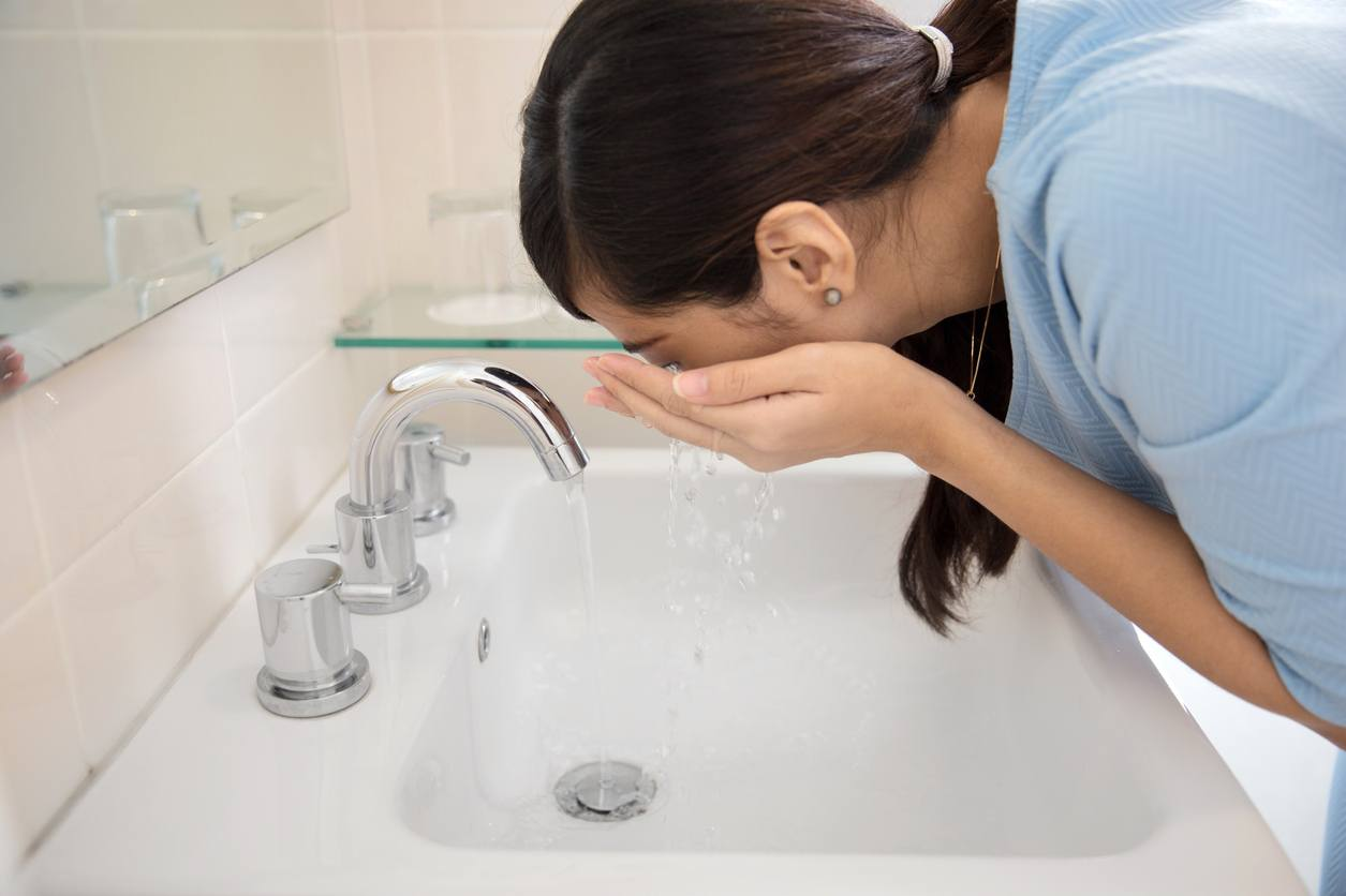 Asian woman washing her face on the sink