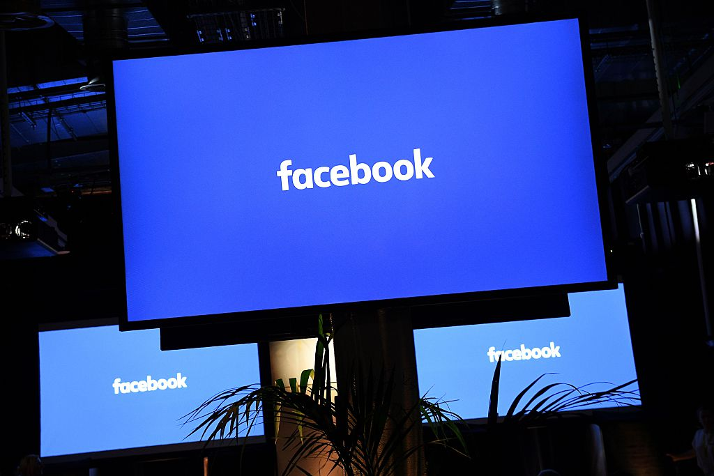 """A Facebook logo is pictured on a screen ahead of a press conference to announce the launch of it's latest product """"Workplace"""""""