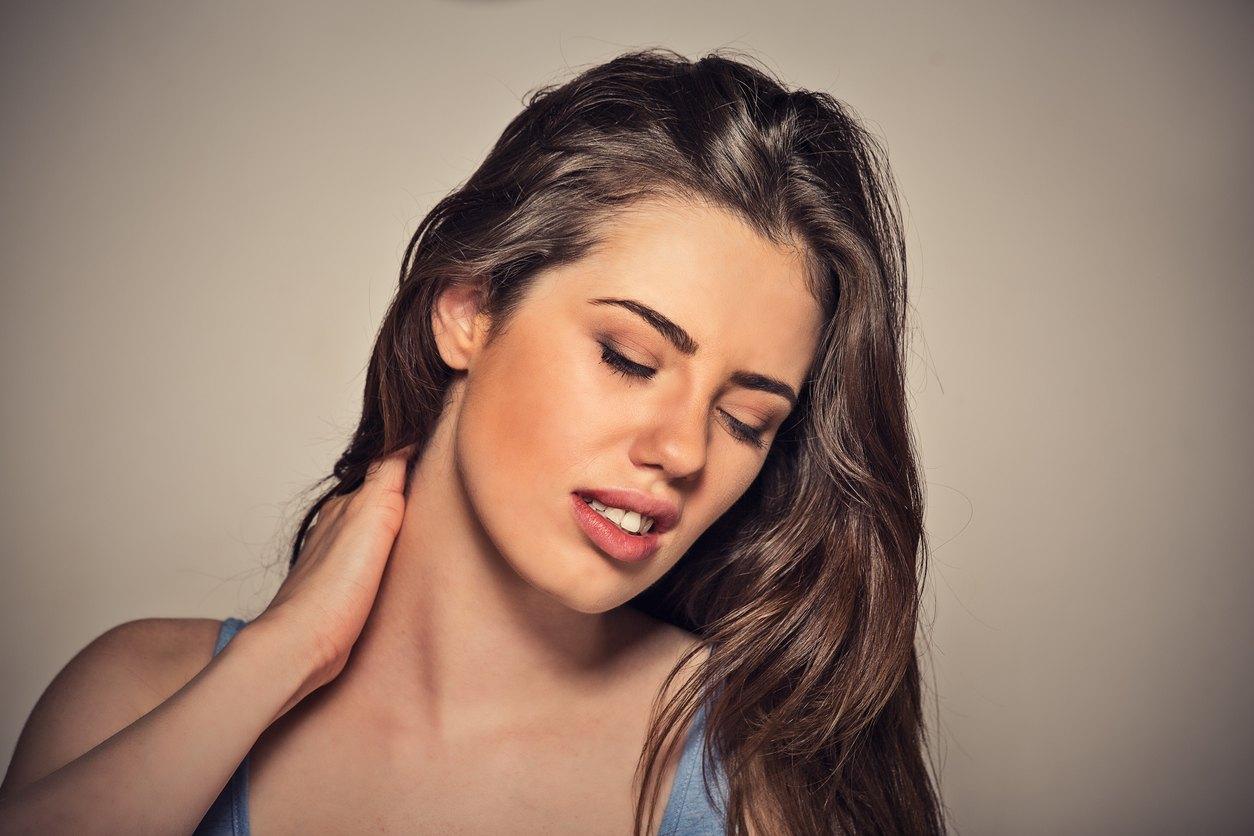 woman massaging her painful neck