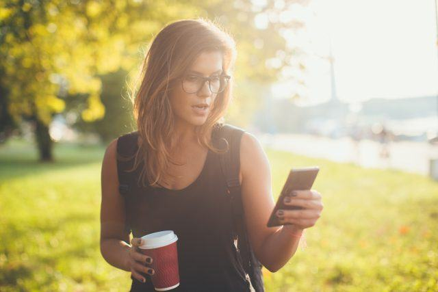 Young woman holding her phone and coffee