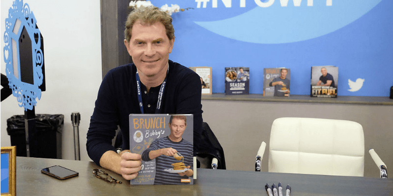 Bobby Flay is sitting down and holding up his cookbook.