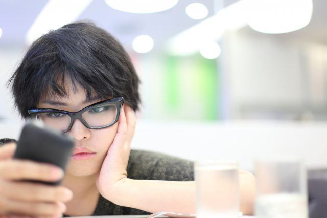A woman with glasses looking at her smart phone.