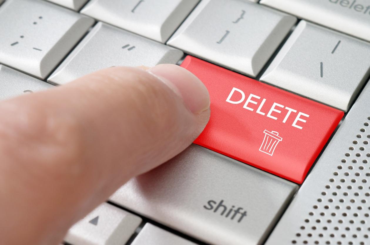 male finger pointing delete key on a metallic keyboard