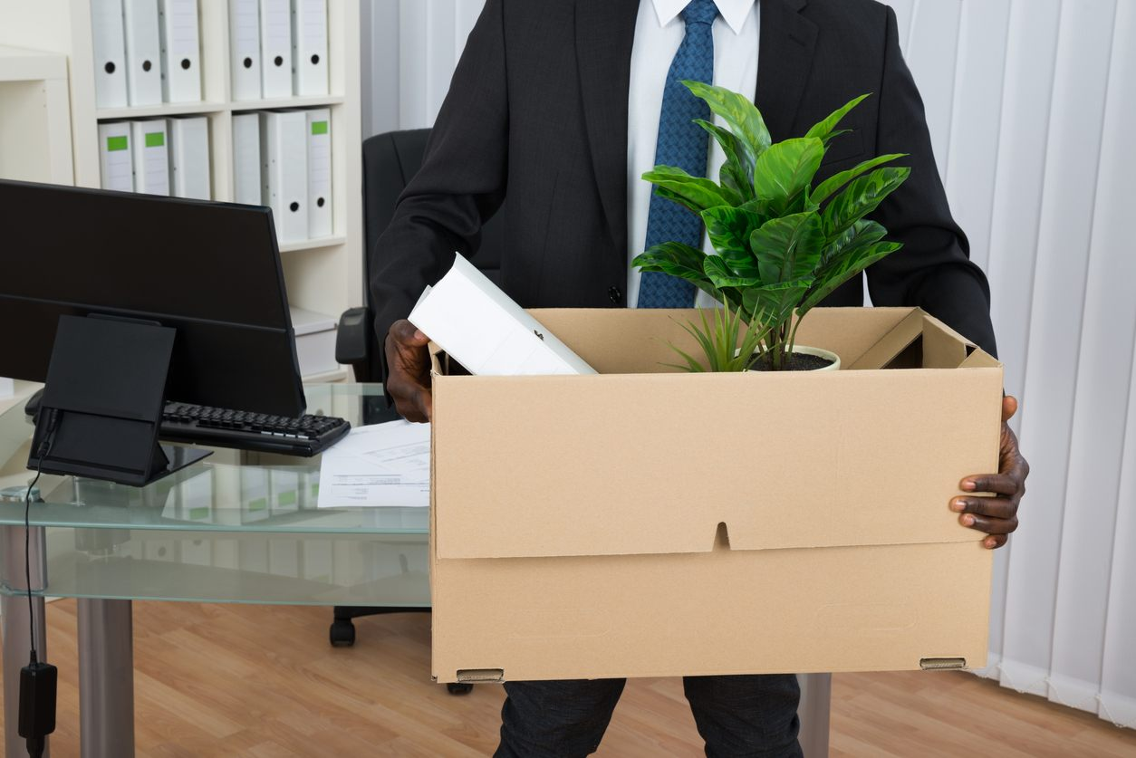 man in suit holding box of belongings