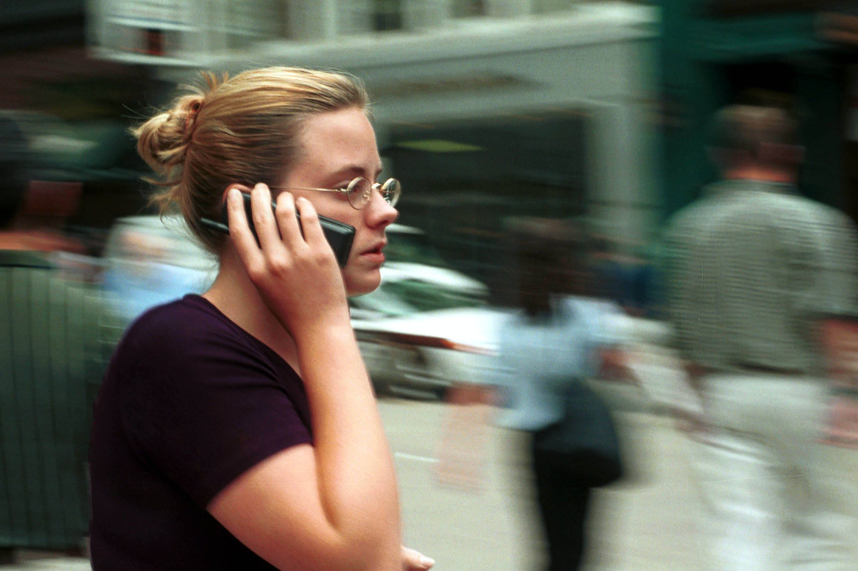A woman uses her cellphone while walking down the street