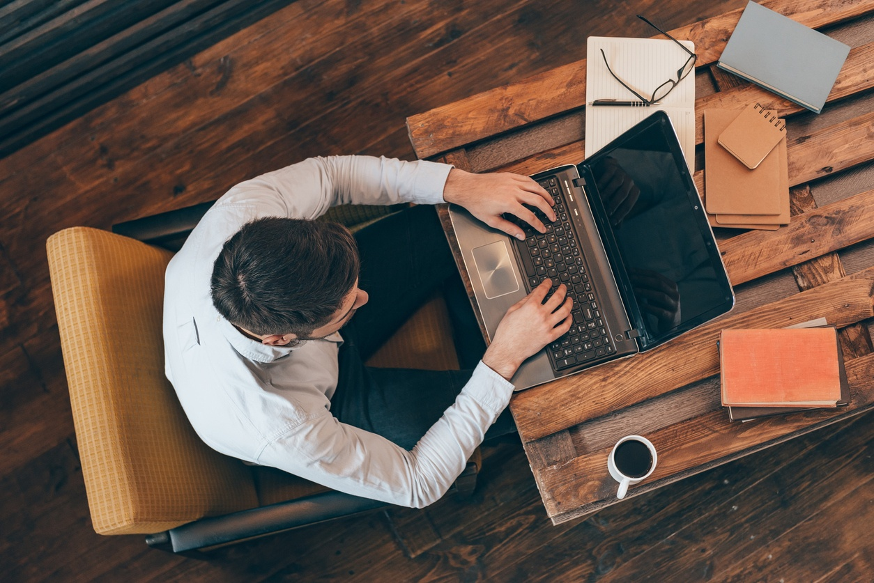 young man working on laptop while sitting at his working place