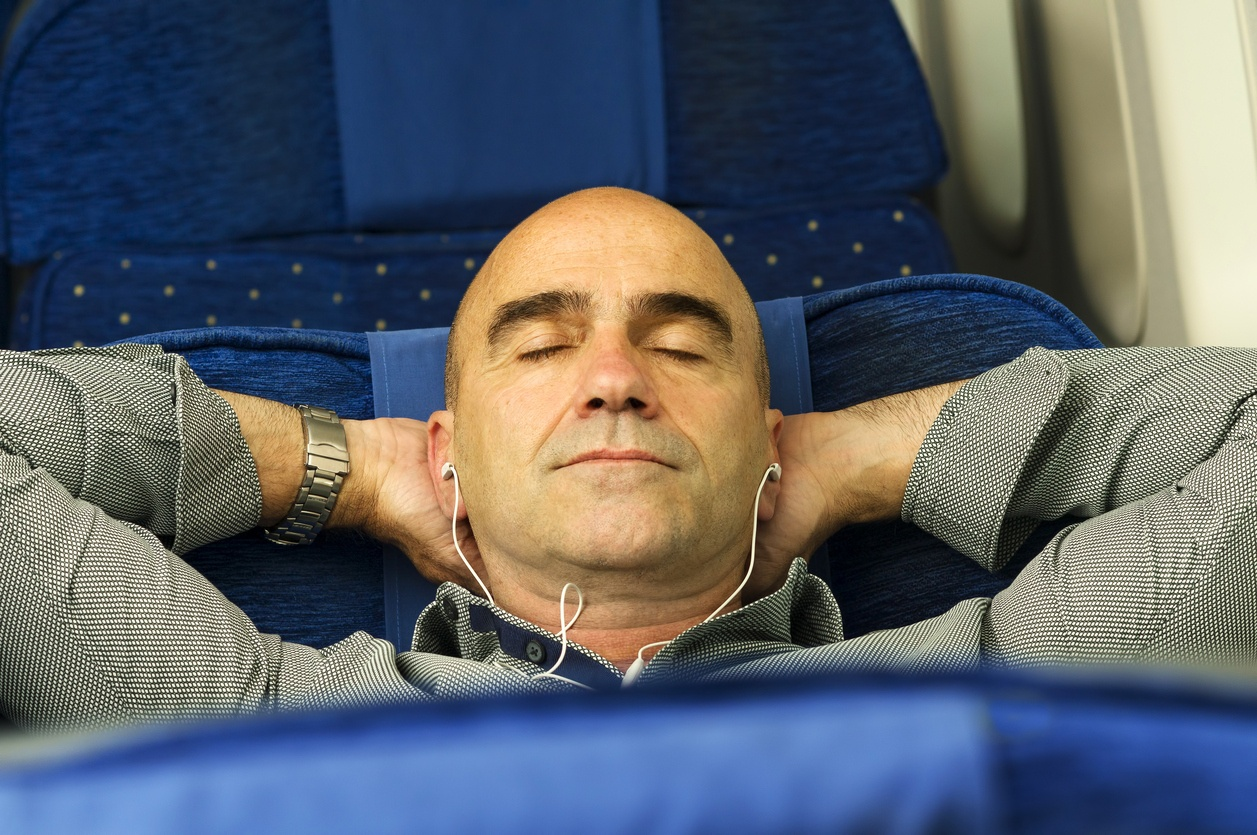 man passenger in airplane using mobile smart device with headphones