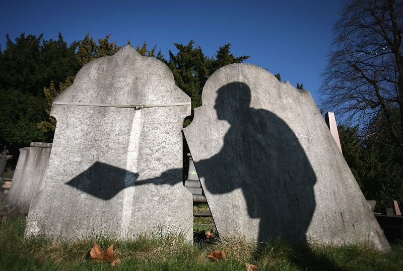 The shadow of a cemetery worker is cast on reclaimed gravestones