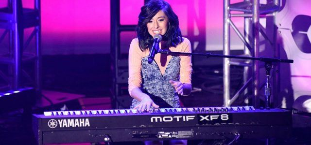Christina Grimmie singing and playing on a keyboard.