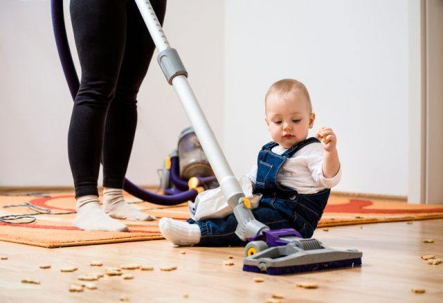Woman cleaning with vacuum cleaner while baby is sitting on floor