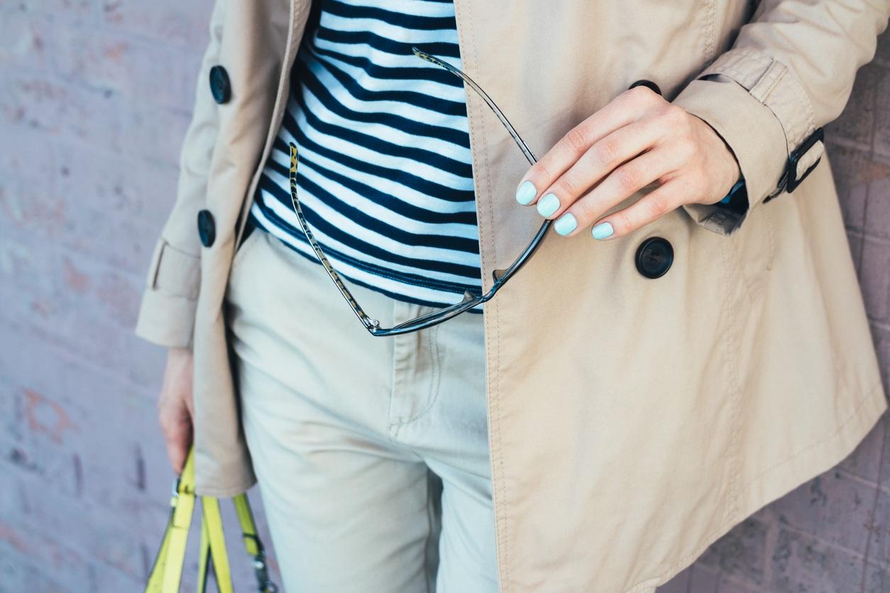 woman in beige coat holding sun glasses