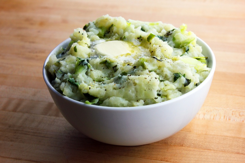 colcannon with a pat of butter in a white bowl