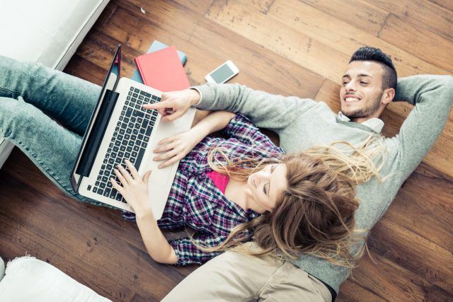 Couple looking at computer while lying on the floor