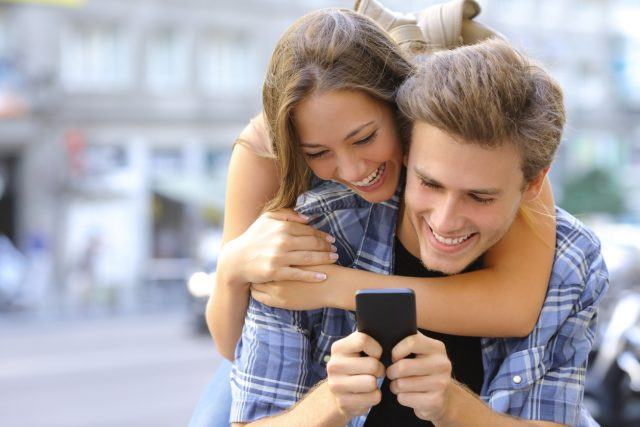 Couple laughing and having fun with a smart phone.