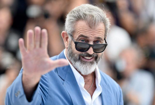 Mel Gibson smiling and waving at the camera, wearing a blue suit and sunglasses.