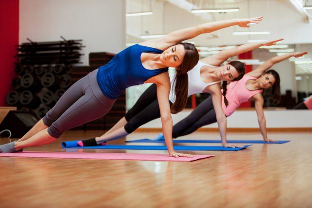 A group of women practices the side plank yoga pose in a studio