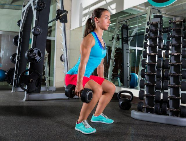 woman doing dumbbell squat at gym