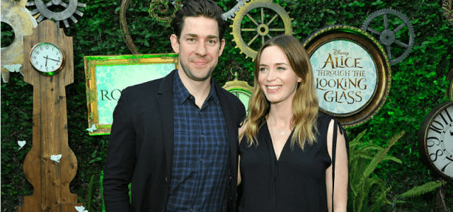 Emily Blunt and John Krasinski smile while being photographed.