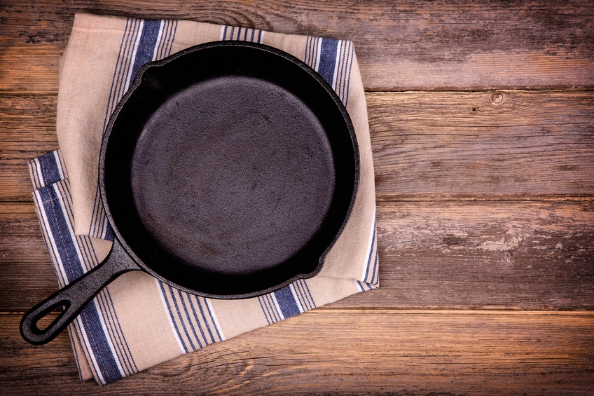 Empty cast iron skillet with tea towel