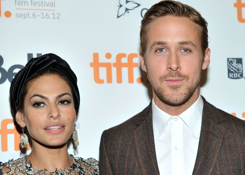 Ryan Gosling and Eva Mendes stand next to each other while posing for photos at a red carpet event.