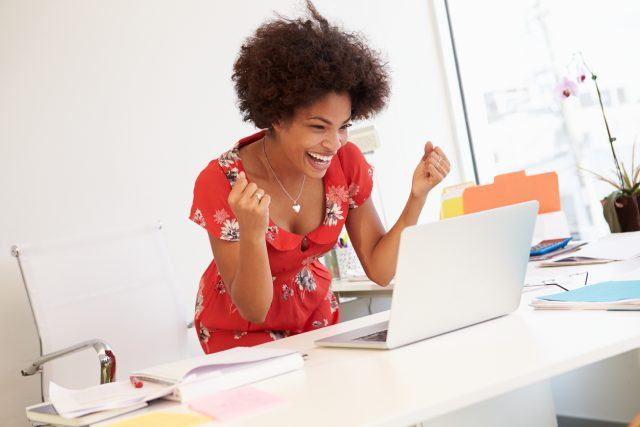 A woman stands behind her desk in excitement at the news of the job perks and benefits she was able to negotiate during her job offer