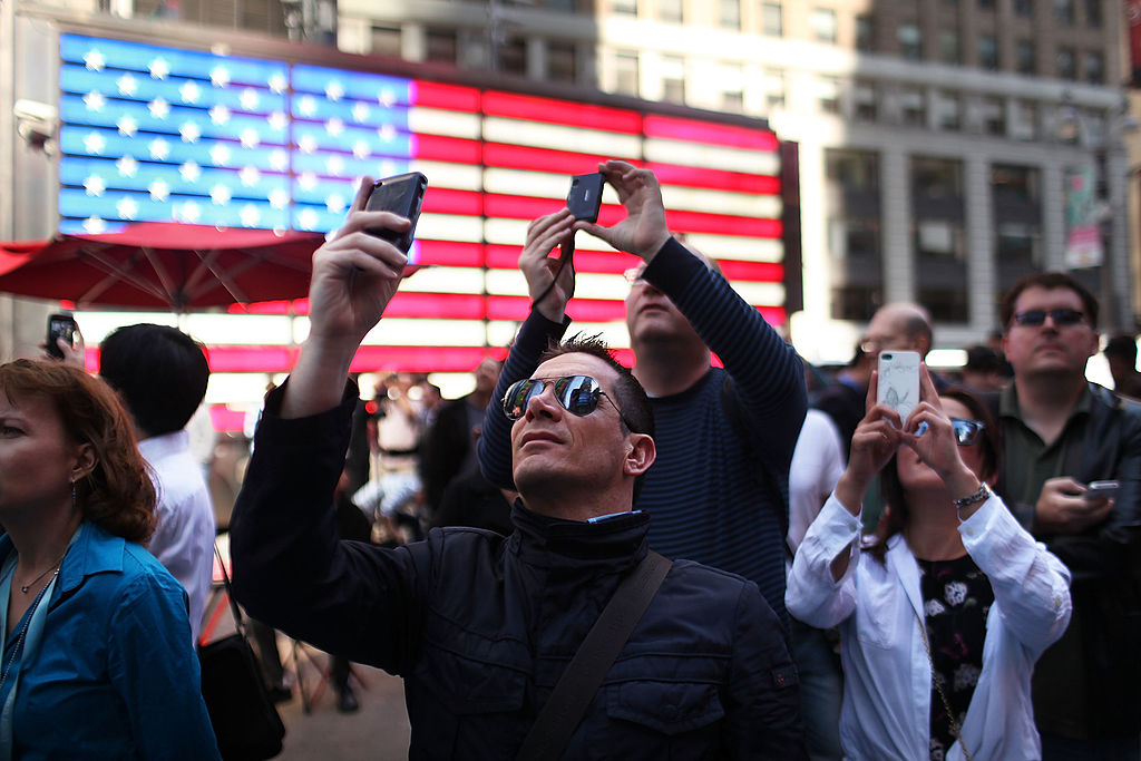 People take pictures as Facebook founder Mark Zuckerberg is viewed on a screen in Times Square