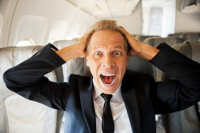 A shocked man sits in an empty airplane