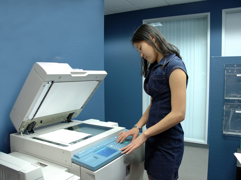A young Asian girl working on copying machine