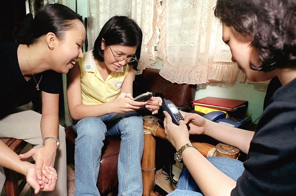 Filipino teenagers check their mobile phones for Y2K bug problems