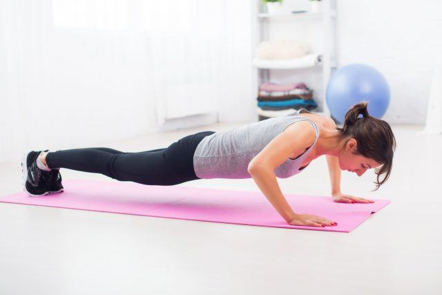 fit woman doing push-ups on the floor