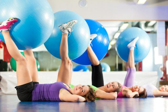 women in an exercise class holding stability balls between their legs
