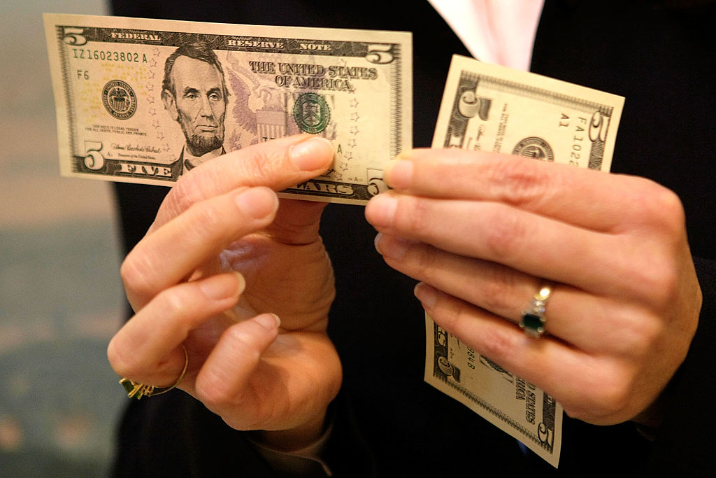 woman holds a $5 bill