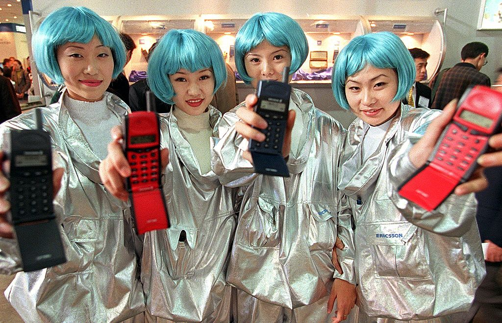 Four Chinese women, wearing blue wigs, display their company's latest mobile phones