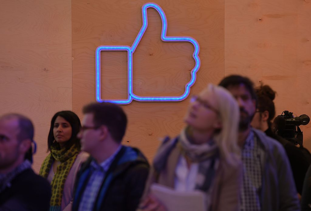 People are seen in front of an light installation during a press preview of the Facebook Innovation Hub
