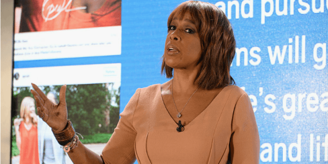 Gayle King standing and waving her hand while at a presentation.
