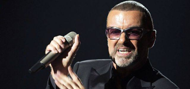 George Michael holding a microphone while wearing a black suit.