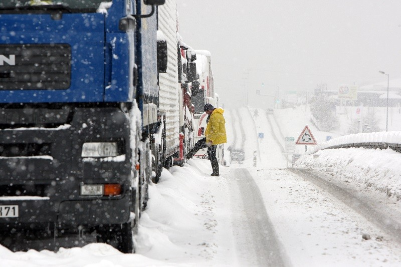 A driver waits outside his truck as vehicles stuck on a snowy road
