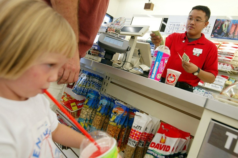 A 7-11 employee sells soda and Slurpees to a man and his children