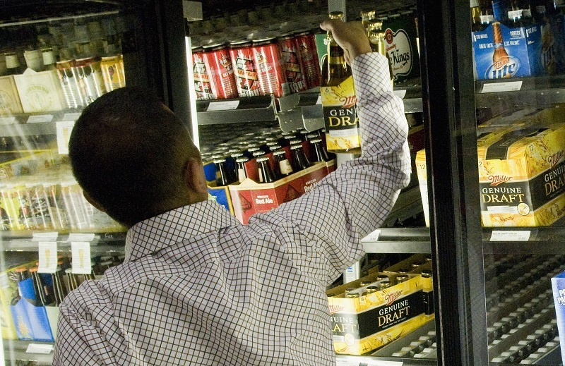 A customer picks out a six pack at a liquor store