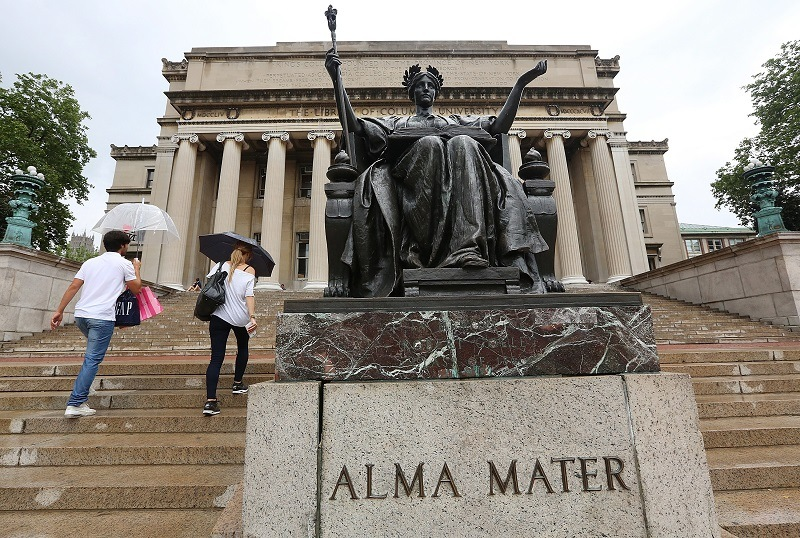 Students walk past the Alma Mater statue on the Columbia University campus, trying not to think about their hefty student loans