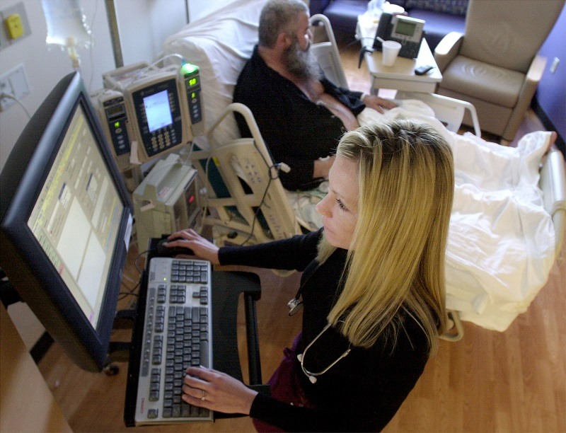 A nurse works on a bedside workstation at a hospital
