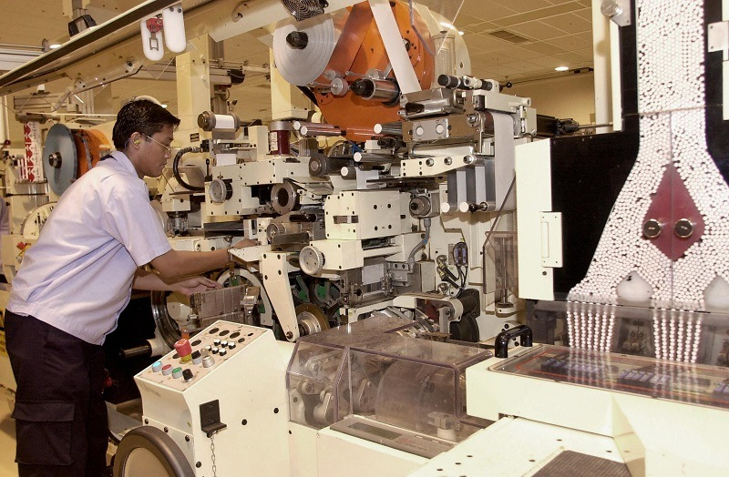 A laborer works at an automated cigarette packaging machine in a Philip Morris tobacco factory
