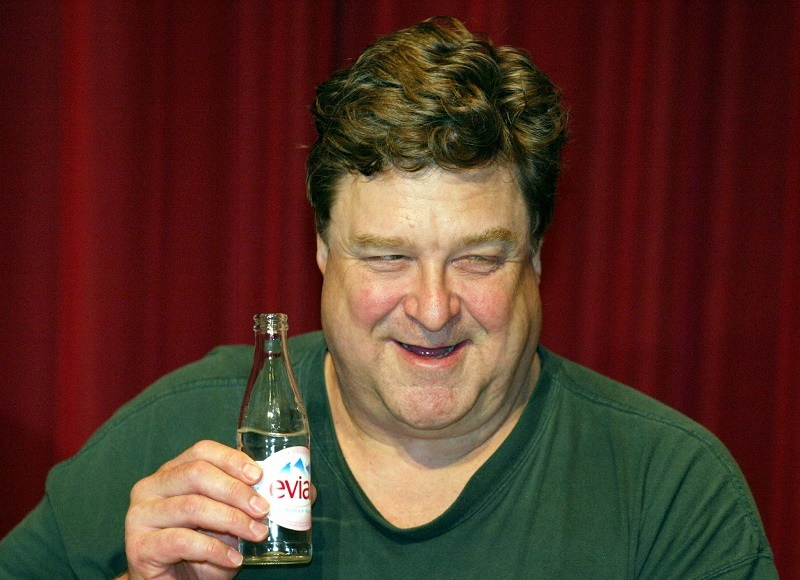 """POTSDAM, GERMANY: US actor John Goodman holds a bottle of water during a press conference at Studio Babelsberg in Potsdam, 20 November 2003. Goodman shoots the movie """"Beyond The Sea"""" a biographic picture about the late '50s rock and roll singer Bobby Darin."""